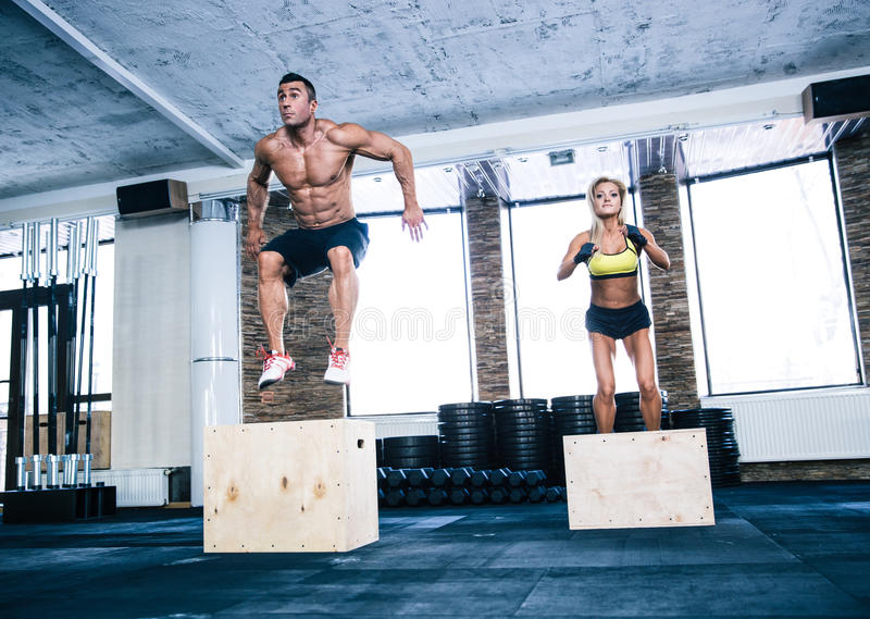 Group of man and woman jumping on fit box stock images