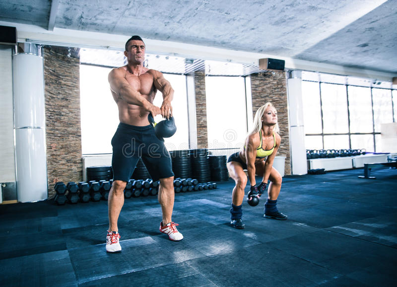 Group of a man and woman workout with kettle ball. Group of a men and women workout with kettle ball at gym royalty free stock images