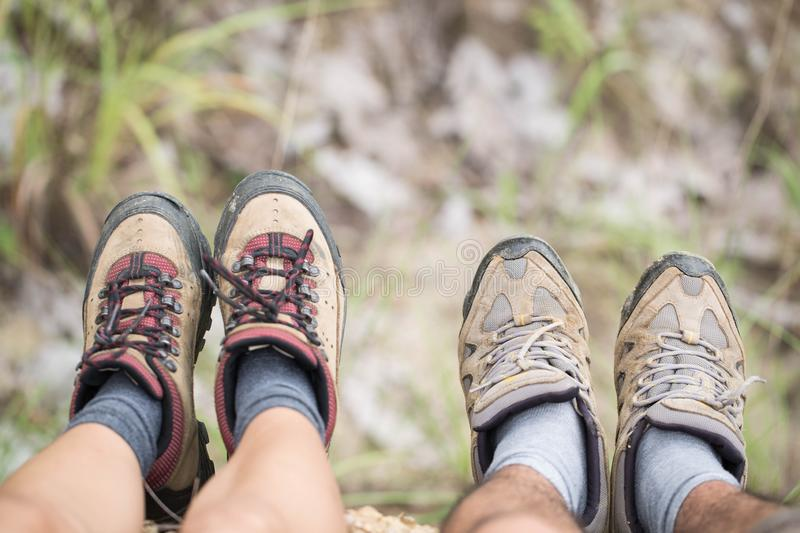 Group of man and women are walking trough forest path wearing mountain boots and walking sticks. Low section view.  royalty free stock photos