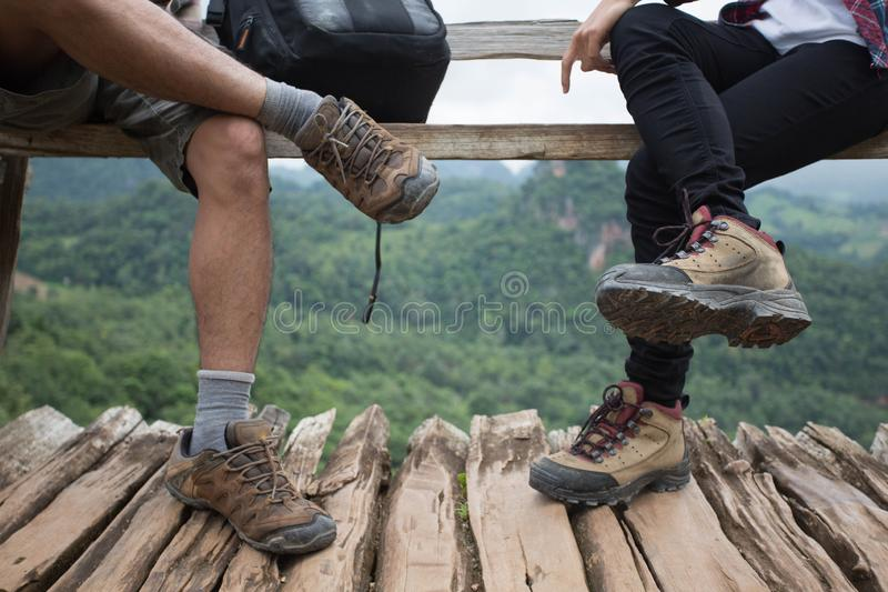 Group of man and women are walking trough forest path wearing mountain boots and walking sticks. Low section view. Group of men and women are walking trough royalty free stock photos