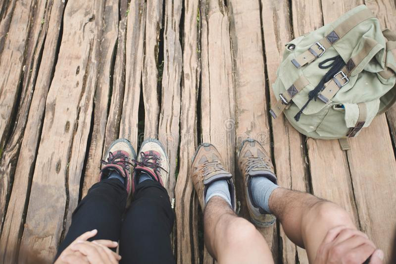 Group of man and women are walking trough forest path wearing mountain boots and walking sticks. Low section view. Group of men and women are walking trough royalty free stock image