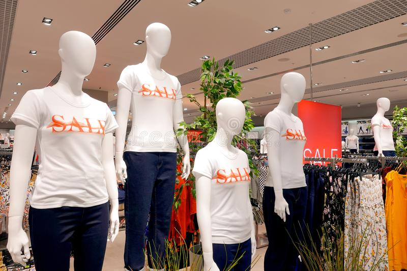 A group of mannequins in a boutique dressed in white t-shirts with the word `sale` printed in red on them. Retail store sale display with a group of mannequins royalty free stock image