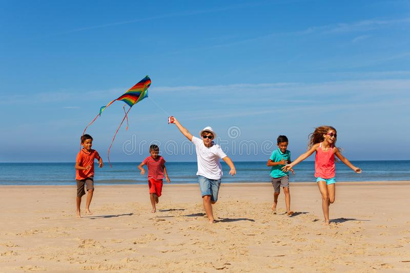 Group of many kids run with kite on a sand beach royalty free stock images