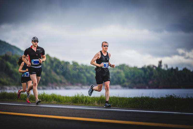 Group of Marathoners at about 7km of distance. CARLETON, CANADA - June 4, 2017. During the 5th Marathon of Carleton in Quebec, Canada. Group of Marathoners at stock photos