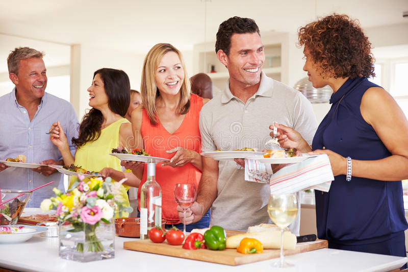 Group Of Mature Friends Enjoying Buffet At Dinner Party stock images