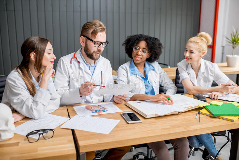 Group of medical students in the classroom. Multi ethnic group of medical students in uniform having a discussion sitting together at the desk with different stock images
