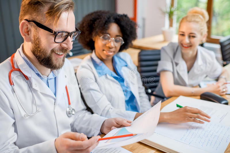 Group of medical students in the classroom. Multi ethnic group of medical students in uniform having a discussion sitting together at the desk with different stock photo