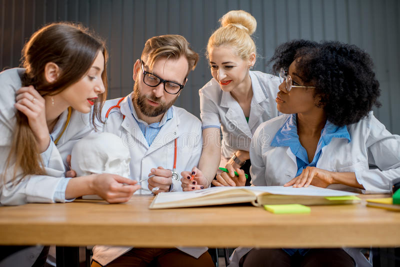 Group of medical students in the classroom. Multi ethnic group of medical students in uniform having a discussion sitting together at the desk with different royalty free stock image