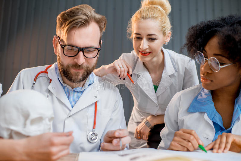 Group of medical students in the classroom. Multi ethnic group of medical students in uniform having a discussion sitting together at the desk with different royalty free stock photos