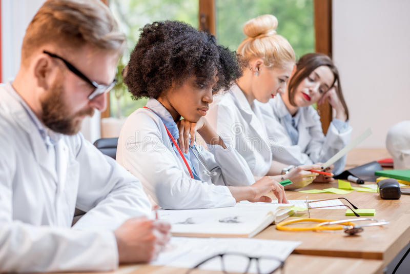 Group of medical students in the classroom. Multi ethnic group of medical students in uniform having a discussion sitting together at the desk with different stock photography