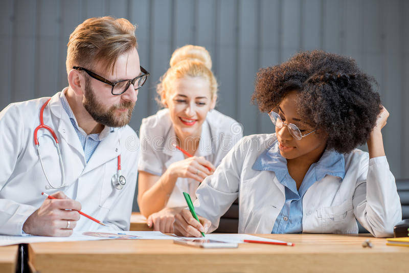 Group of medical students in the classroom. Multi ethnic group of medical students in uniform having a discussion sitting together in the modern classroom royalty free stock image