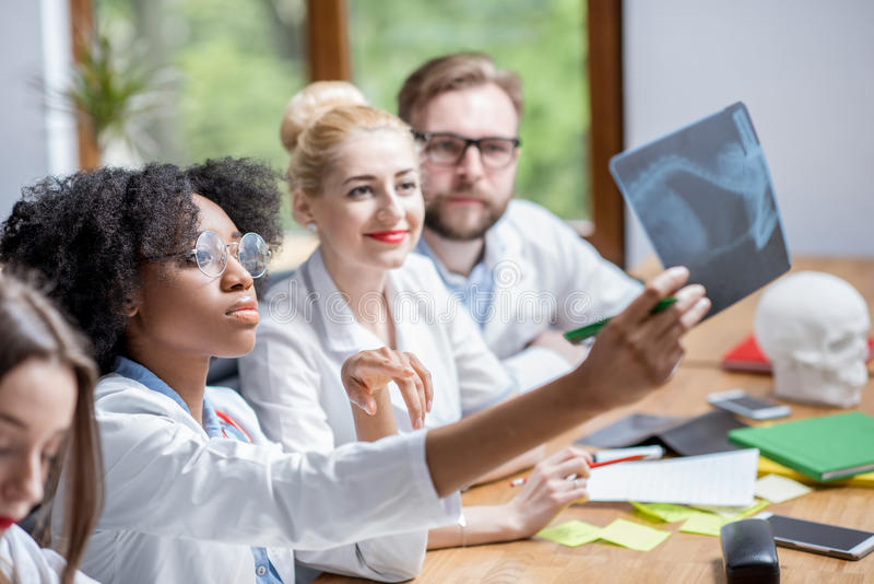 Group of medical students in the classroom. Multi ethnic group of medical students in uniform looking on the x-ray sitting at the desk in the modern classroom royalty free stock photo