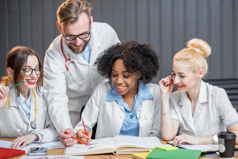 Group of medical students in the classroom. Multi ethnic group of medical students in uniform studying together sitting at the desk with books in the modern stock photography