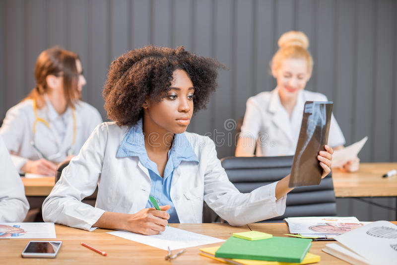 Group of medical students in the classroom. Multi ethnic group of medical students in uniform working on medical research sitting at the desk with x-ray and royalty free stock images