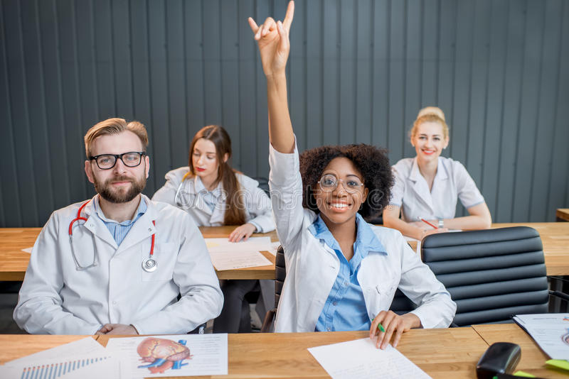 Group of medical students in the classroom. Medical students raising hands wanting to answer sitting at the desk during the lesson stock photo