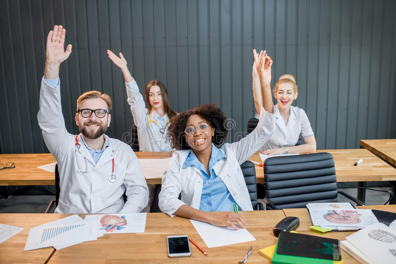 Group of medical students in the classroom. Medical students raising hands wanting to answer sitting at the desk during the lesson stock photography