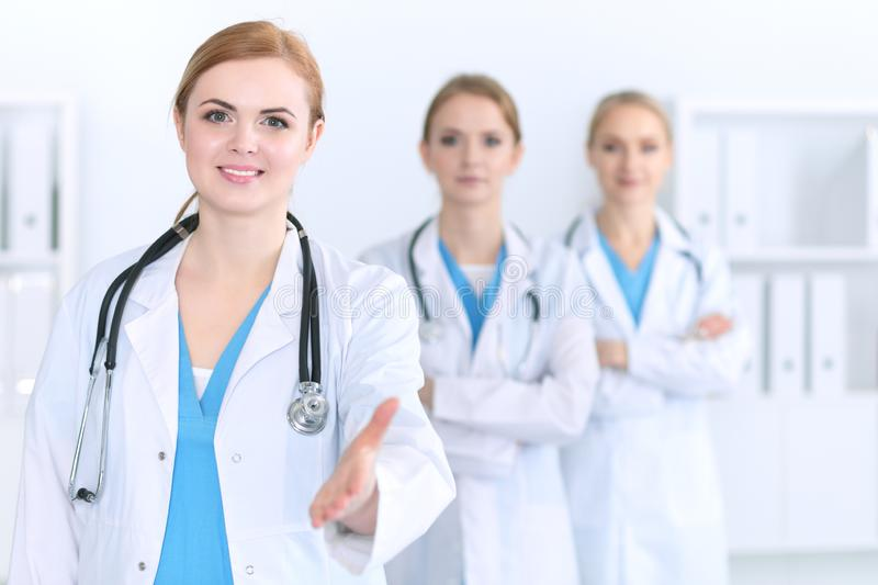 Group of medicine doctors offering helping hand for shaking hand or saving life. Partnership and trust concept in healt. H care or medical cure stock photos