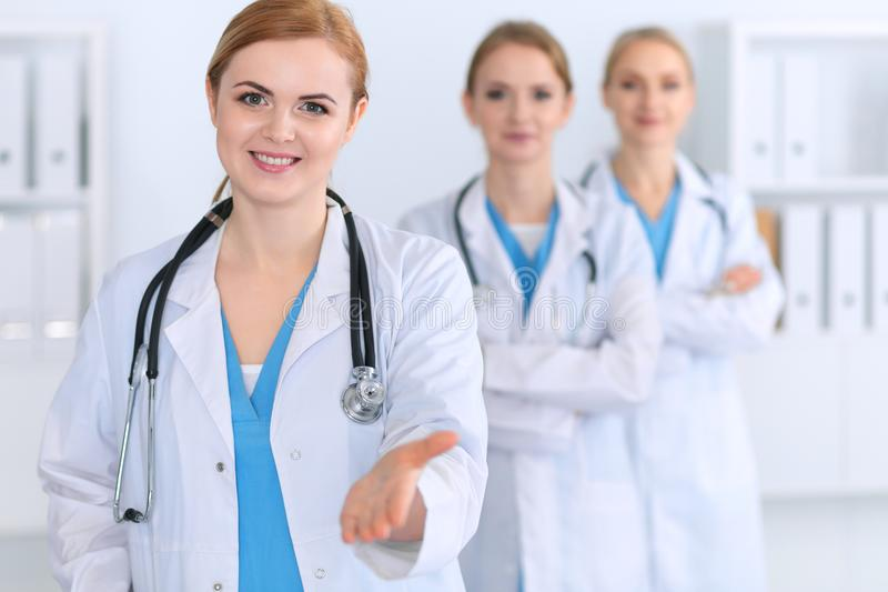 Group of medicine doctors offering helping hand for shaking hand or saving life. Partnership and trust concept in healt. H care or medical cure stock image