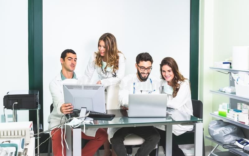 Group of medicine students at health care clinic working on computer research. Group of medicine students at health care clinic - Pharmacy university college royalty free stock photo