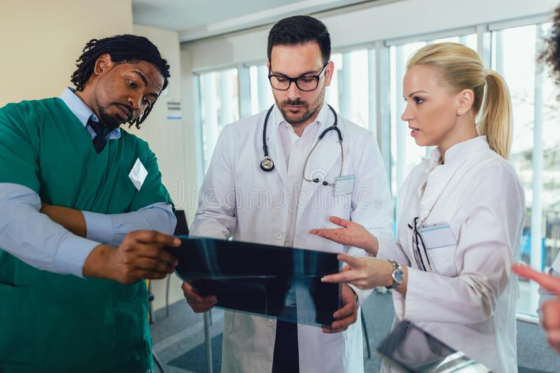 Group of medics discuss x-ray scan. In office royalty free stock photo