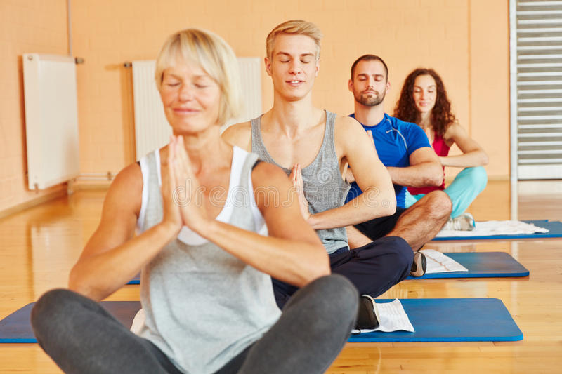 Group meditates in yoga class stock photography