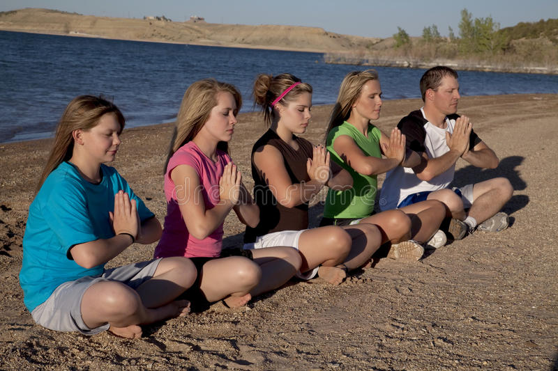Group meditating. A family sitting in the sand doing a yoga pose and meditating together royalty free stock photo