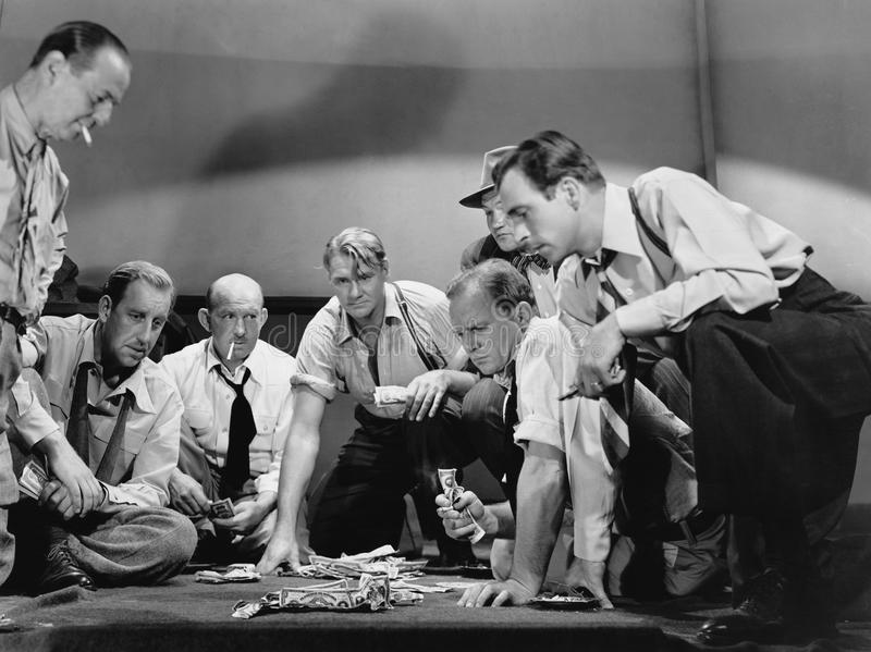 Group of men gambling. (All persons depicted are no longer living and no estate exists. Supplier grants that there will be no model release issues stock photo