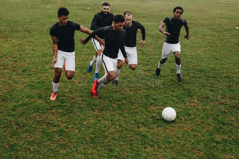 Group of men playing football on the field running for the ball. Soccer players running on field for possession of the ball.  royalty free stock photography