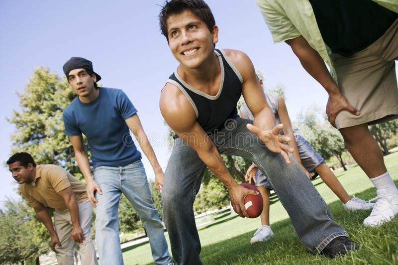 Group of men playing football in park royalty free stock image