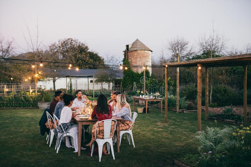 Group of men and women having outdoors party. In restaurant. friends sitting around a table and having dinner stock photography