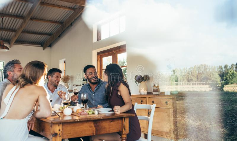 Friends enjoying meal at home together royalty free stock photo