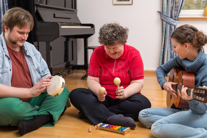 A group with a mentally disabled woman enjoys the music therapy royalty free stock photo