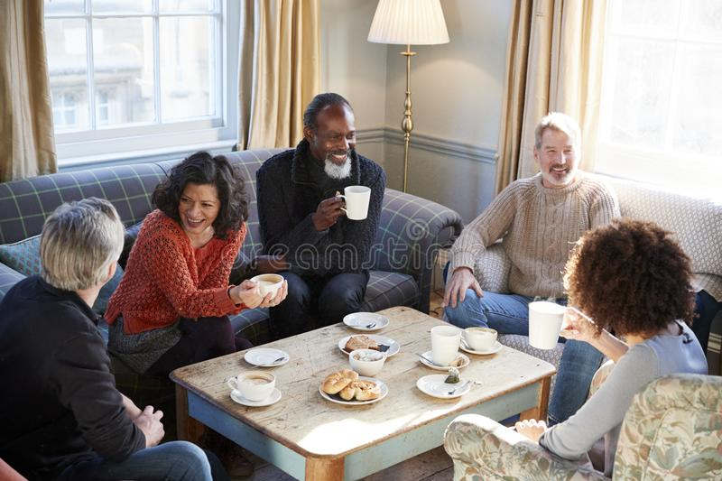 Group Of Middle Aged Friends Meeting Around Table In Coffee Shop royalty free stock photos