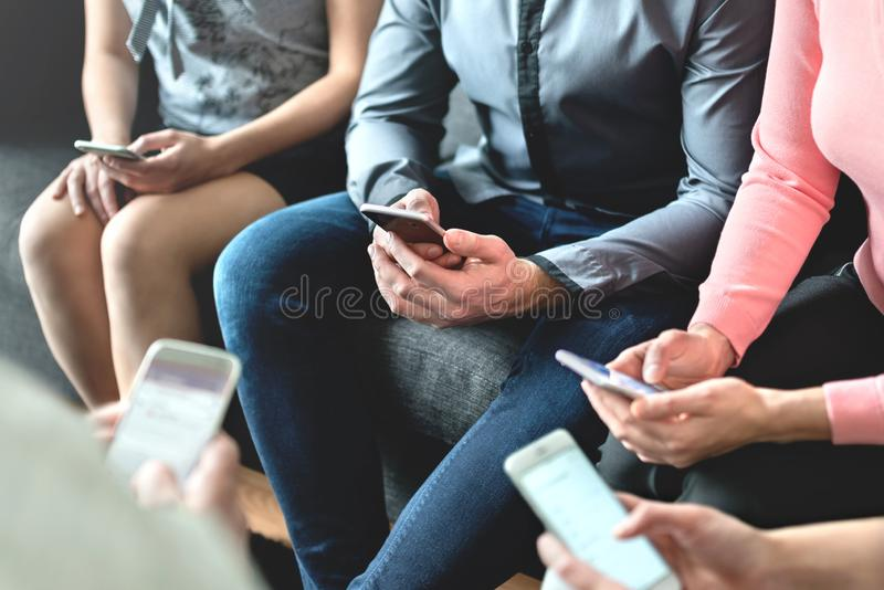 Group of millennial business people using mobile phones and sitting on couch. Networking and teamwork. Working on project. stock photos