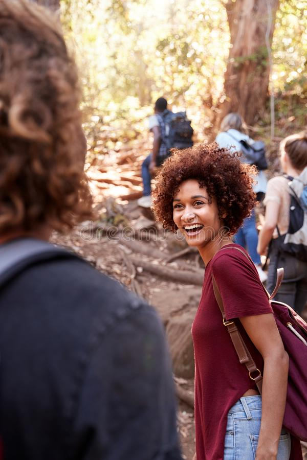 Group of millennial  friends hiking up hill on a forest trail, vertical stock photography