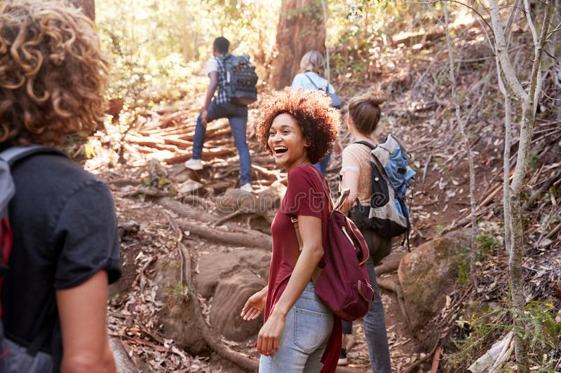 Group of millennial  friends hiking uphill on a forest trail, three quarter length stock image