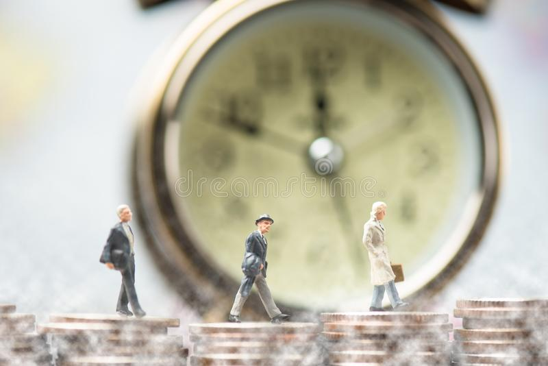 group of miniature businessmen walking on coin stack stock photos