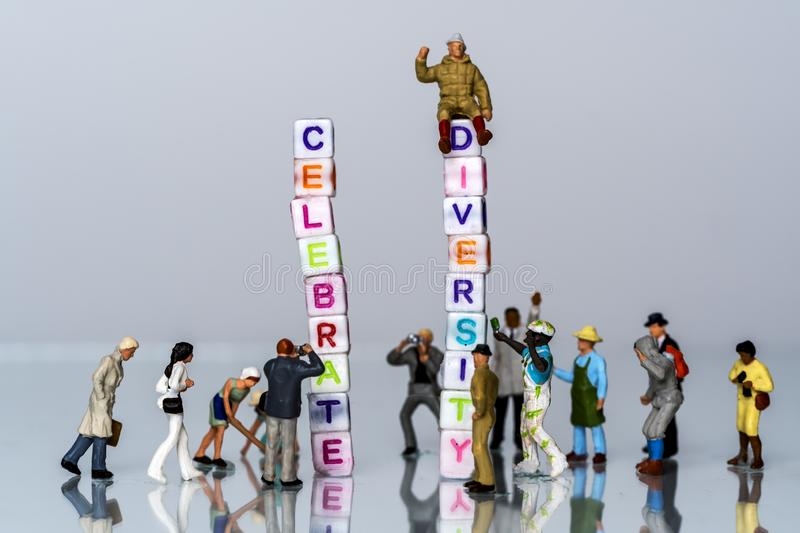 Group of Miniature diverse figurines people walking around a Group Of Letters forming Words Spelling stock images