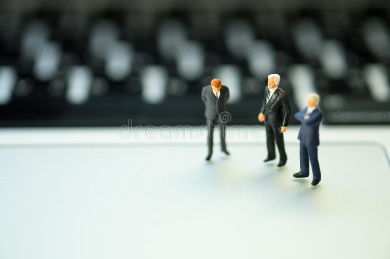 Group of miniature people businessmen collaborate help and work as team. Standing on laptop computer looking at enemy. Teamwork in business strategy concept stock photos