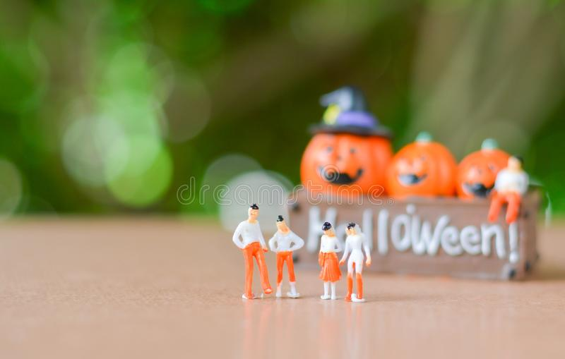 Group of Miniature people, small model human figure with blurry pumpkin jack with green bokeh for background. Copy space for your royalty free stock photography