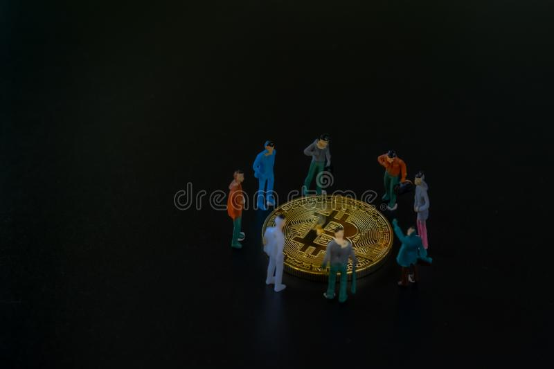 Group of Miniature people, small model human figure standing around on golden Bitcoins on dark background with copyspace for your stock photography