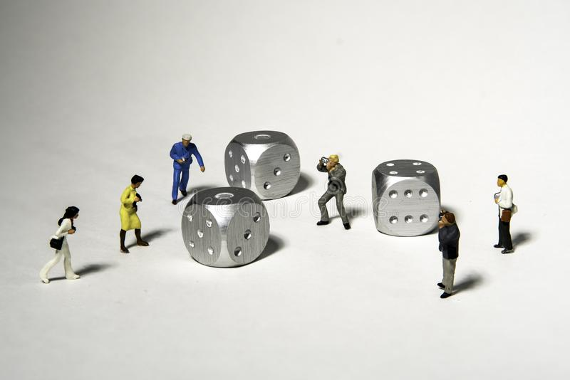 Group of Miniature Photographers take Pictures of three silver dice royalty free stock photo