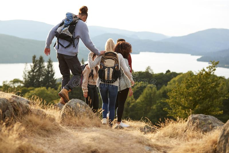 A group of mixed race young adult friends descending after a mountain hike, back view stock image