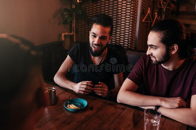 Group of mixed race young men talking and laughing in lounge bar. Multiracial friends having fun in cafe. Guys hangout royalty free stock photo