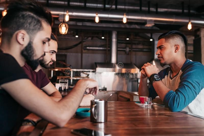 Group of mixed race young men talking and laughing in restaurant. Multiracial friends having fun in cafe. Guys hangout royalty free stock photography