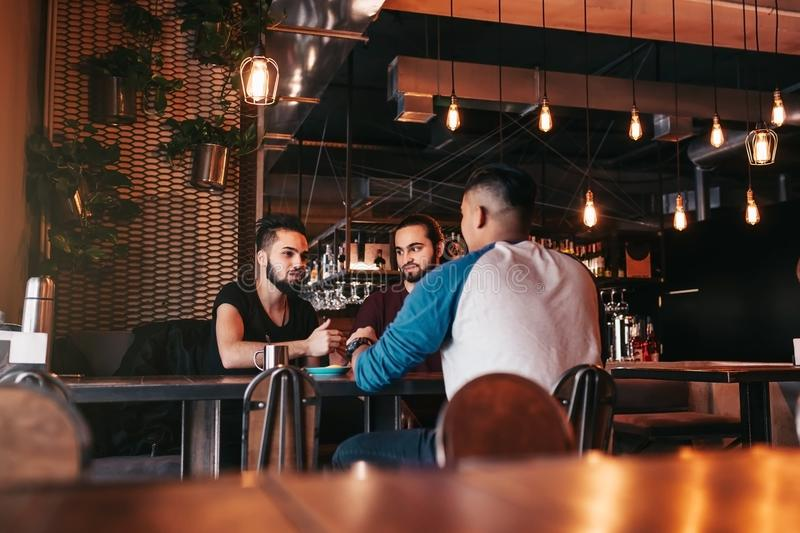 Group of mixed race young men talking in lounge bar. Multiracial friends hanging out and having fun in cafe stock photography