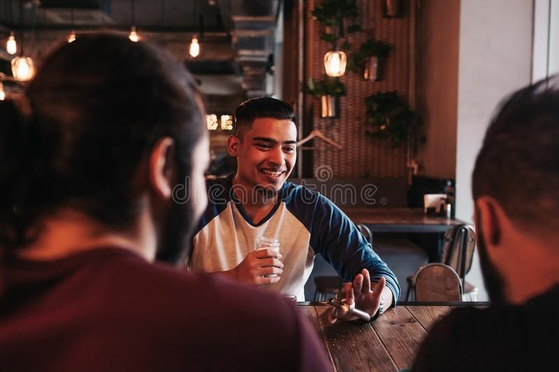 Group of mixed race young men talking and laughing in lounge bar. Multiracial friends having fun in cafe stock photo