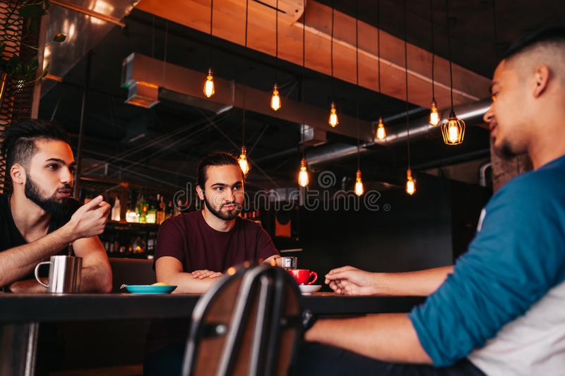 Group of mixed race young men talking and laughing in lounge bar. Multiracial friends having fun in cafe. Guys hang out royalty free stock photo