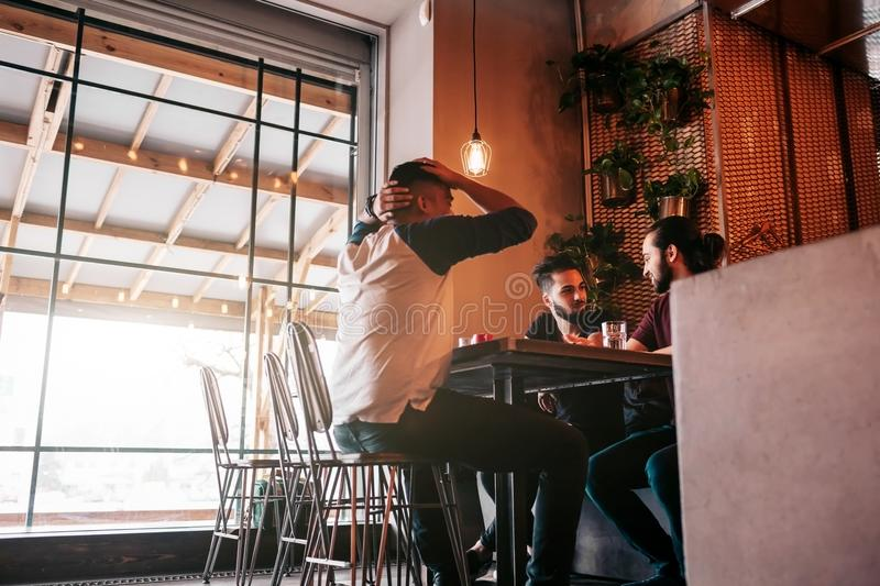 Group of mixed race young men talking in lounge bar. Multiracial friends hanging out and having fun in cafe stock image