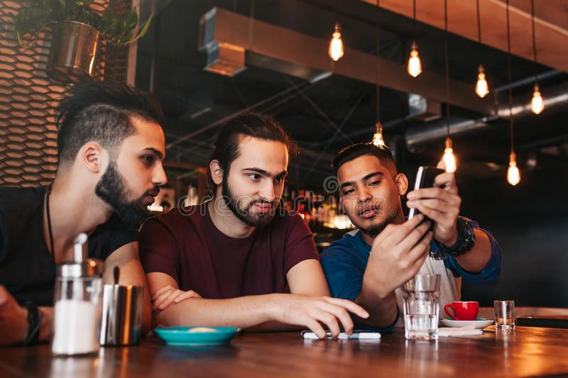 Group of mixed race young men talking in lounge bar. Multiracial friends having fun in cafe. Guys hanging out stock photo